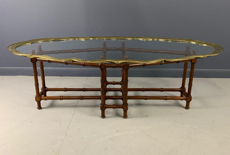 Vintage faux bamboo coffee/cocktail table features metal frame and glass tray top rimmed in solid brass. Good vintage condition with minor imperfections consistent with age.