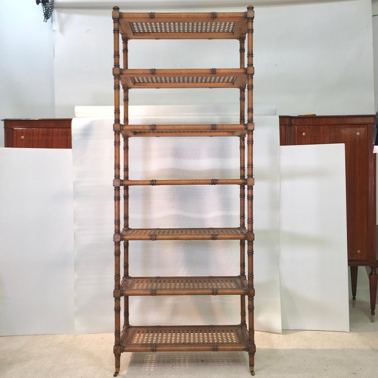 Hollywood Regency cum George IV-style étagère in faux bamboo wood in a provincial pecan finish and having seven caned open shelves, raised on four legs with brass casters. Finished on all sides so as to float freestanding within a room.