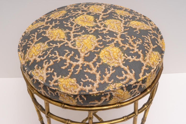 This stylish and chic vanity stool was acquired from a Palm Beach estate and it is very much in the style and quality of pieces designed by Maison Baguès, with its cast brass faux bamboo motif.   Note: The piece was professionally upholstered in a