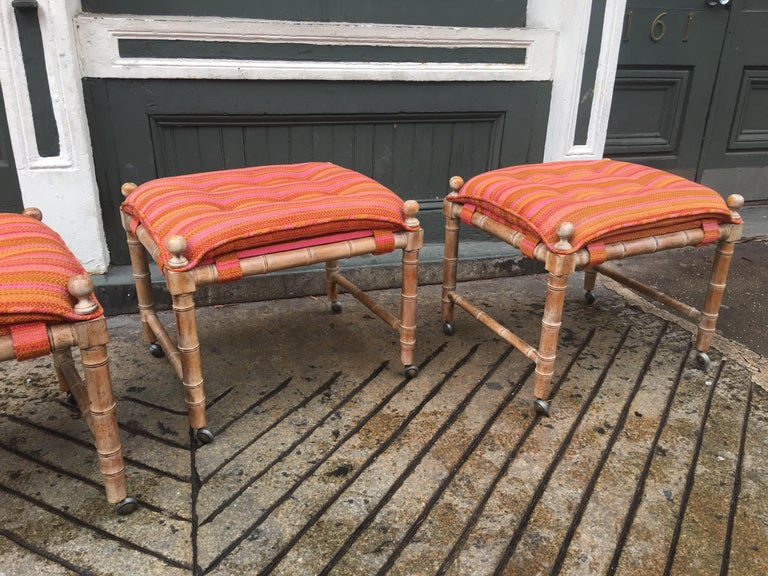 Set of 3 faux bamboo wood stools on wheels. Original Fabric shows wear. We can assist with reupholstering the set. Wood has a slight white wash finish over a light walnut.