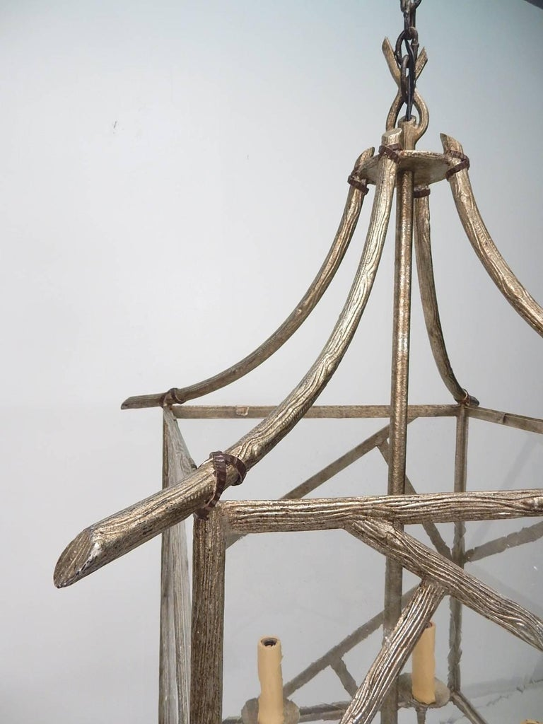 Enormous faux bois twig pagoda chandelier made of brass with platinum finish, circa 1970s. Massive piece measuring over 2 feet wide and 3 feet tall with a 6 foot wrought iron hand forged chain and 8 inch wide matching ceiling cap. Thick mineral