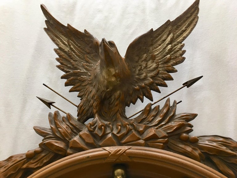 Large Mid-Century Modern sculptural Regency style convex fish eye eagle wall art mirror. The detailed carved faux wood look frame features thirteen gilded balls and a traditional crest with metal arrows and acanthus foliate garland decoration.