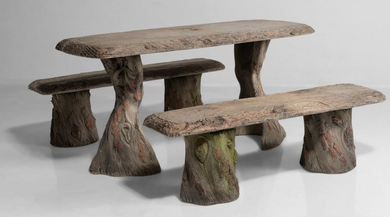"""Faux Bois garden table with benches, France, 20th century.  Cast concrete with detailed carving and weathered paint. Umbrella stand included.  Measures: Table: 59.5"""" W x 29.25"""" D x 29"""" H, bench: 53.5"""" W x 14.75"""" D x 16.5"""" H."""