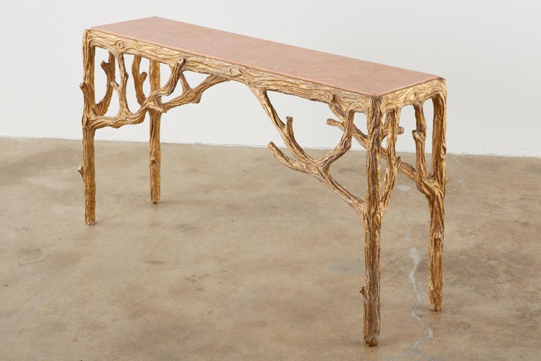 Dramatic faux-bois console or sofa table designed by Horatio Acuna. Features a gesso and gilt finish on the twig branch motif frame. Topped with a faux marble inset finished in a rosé color. Beautifully handcrafted with an aged patina. Signed and