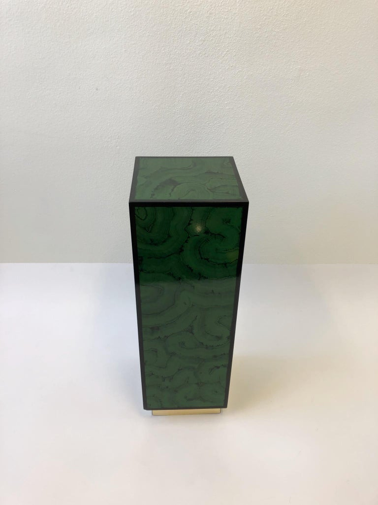 """A glamorous 1970s faux malachite lacquer and brass modern pedestal. The pedestal is constructed of wood that's lacquered in a malachite pattern and outlined black with a brass veneer base. Dimensions: 12"""" deep, 12"""" wide, 36"""" high."""