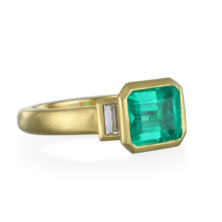 Colombian Emerald flanked by diamond baguettes. The lively green hue is enhanced by Faye Kim's signature 18k matte-finished gold and the sparkle from the side diamonds.  Colombian Emerald - 1.60 Carats Diamonds - .23 Carats twt Size 7  LxW - 9.87 x