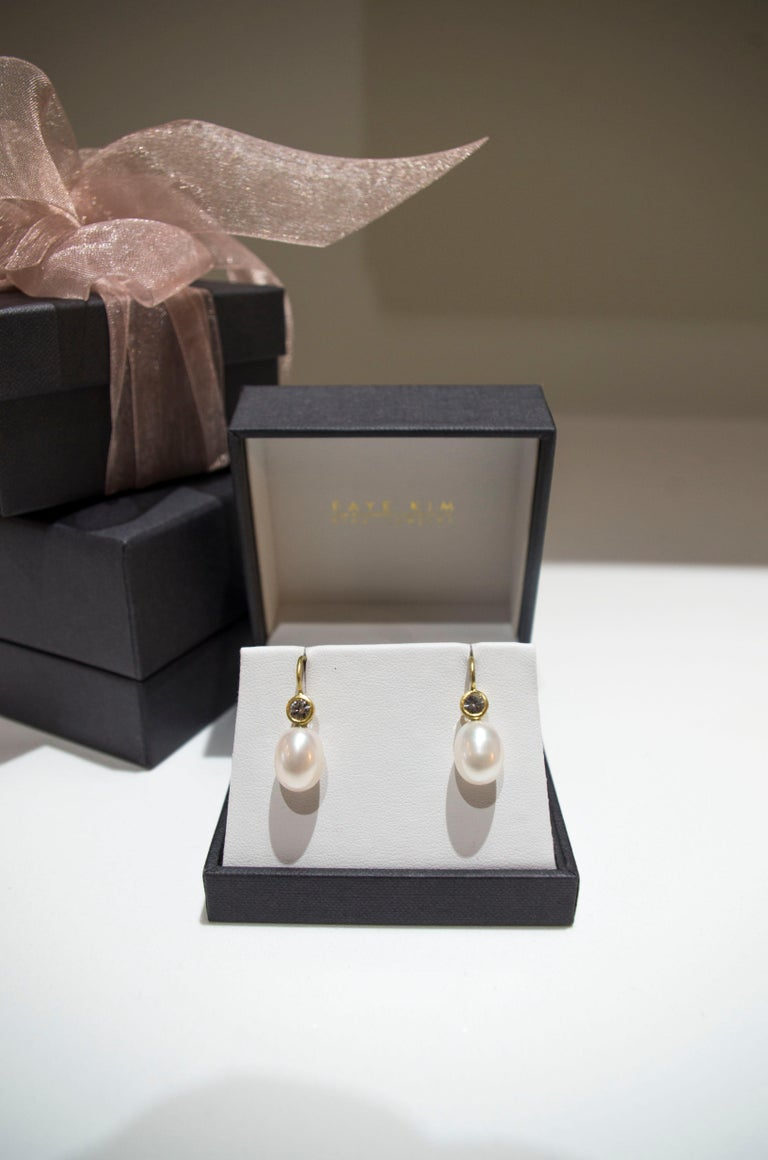 White sapphires set in 18k gold enhance white freshwater pearls to create a pair of modern day classic drop earrings.  Casual or corporate, the clean design is flattering and simply beautiful!  French ear wires.    Approximately 5/8