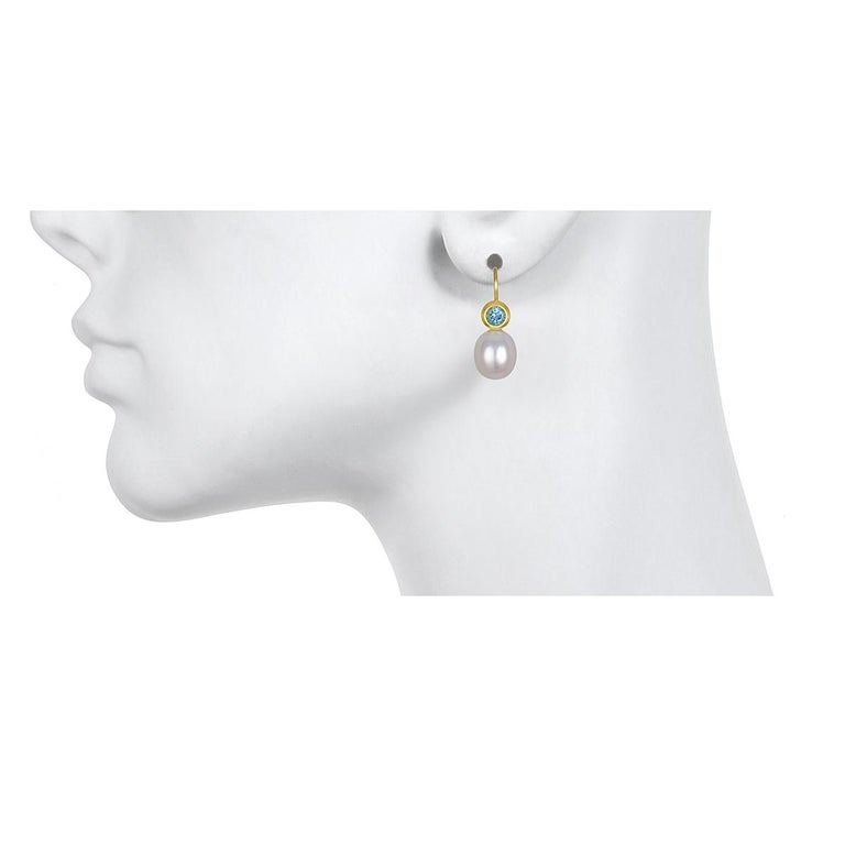 Set in 18k green gold,  beautiful blue Aquamarines are bezel set and paired with lustrous white freshwater pearls to create a pair of modern-day classic drop earrings.  Matte-finished. Casual or corporate, the clean design is flattering and simply