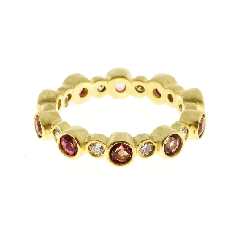 Classic eternity band with bezel set diamonds and pink Tourmaline in 18k gold.  Wear alone or stack with other colors.  This ring is also available with green Tourmaline.    Size 6.5.   Diamonds:  .38 carats twt.    Made in the USA