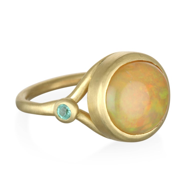 Faye Kim 18k Gold Round Mexican Opal Cabochon and Paraiba Tourmaline Ring. The beautiful color contrast between the bright blue-green Paraiba tourmalines and the Opal perfectly complements one another in this striking Mexican Opal Cabochon and