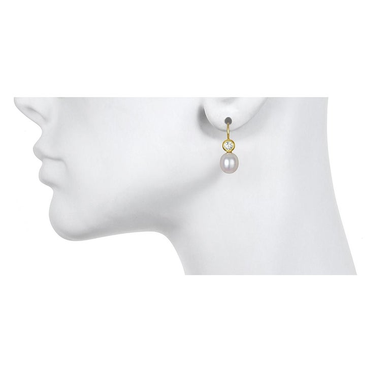 Set in 18k green gold, White Sapphire is paired with white freshwater pearls to create a pair of modern-day classic drop earrings.  Matte-finished. Casual or corporate, the clean design is flattering and simply beautiful!  French ear wires.