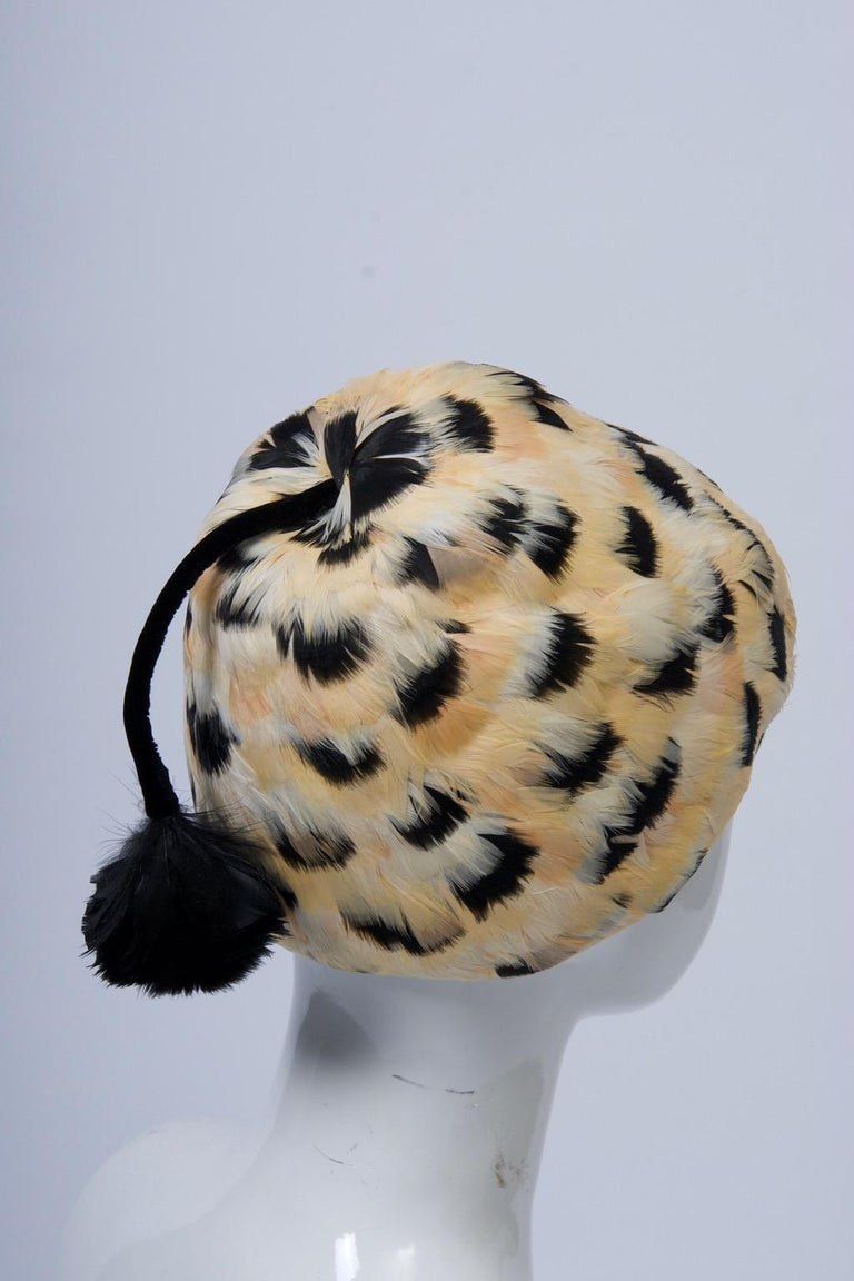 Unusual vintage hat, c.1960, composed of small white, beige, and black feathers arranged in a repetitious pattern on a structured black felt base. The dome-shaped hat is adorned with a velvet cord terminating in a tassel that emerges from the top of