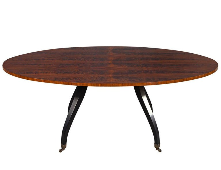 Feathered walnut oval dining table by Baker Furniture. This table has a stunning feathered walnut table top with a hand rubbed satin finish. Sitting atop of a black satin lacquer splayed caster leg base.