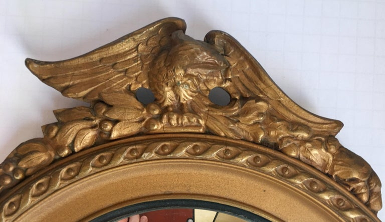 Midcentury round convex giltwood wall mirror featuring a carved eagle with acanthus foliate decoration. This sculptural Regency style convex fish eye eagle mirror is a nice size to incorporate into an art grouping.