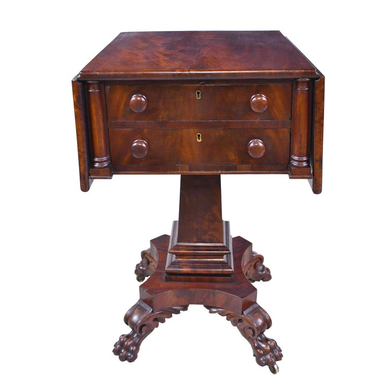 A very handsome Federal work table in fine West Indies mahogany with fold-down leaves. There are two drawers with two rounded columns flanking each side. Drawers have the original turned pulls. Top rests on a square column that gradually widens