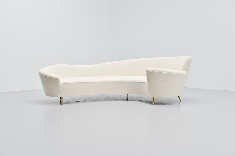 Elegantly curved lounge sofa designed by Federico Munari, Italy 1960. The sofa has a very nice uncommon shape and has solid brass legs. It has solid brass legs and is newly upholstered in very nice white woven fabric. Because of the curved shape,