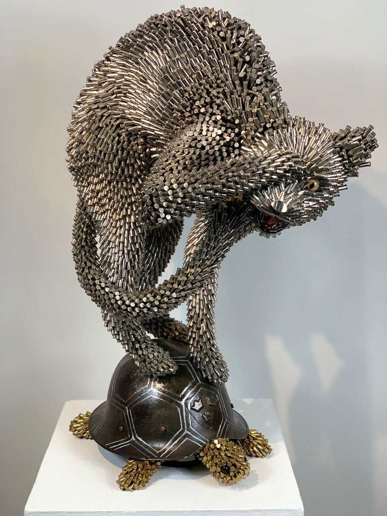 The style, choice of materials, and subject matter is iconically Federico Uribe.  The cat made entirely out of used bullet casing balances on the turtle, whose shell is made of an antique WWI Swedish helmet.  The title,