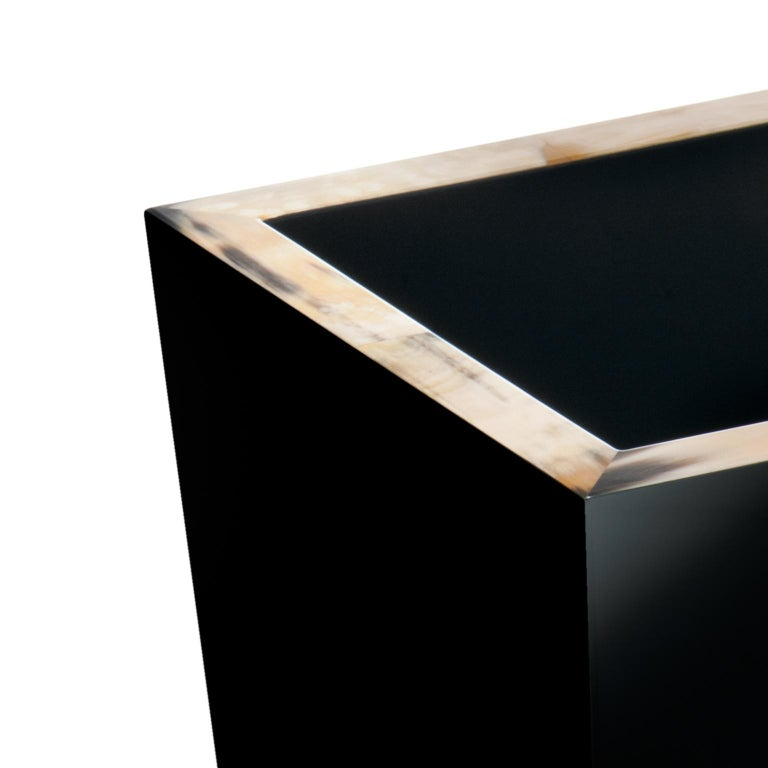 Handcrafted of wood, Fedro waste paper basket features and inverted pyramidal shape finished in high-gloss black lacquer. Embellished by an elegant edging in Corno Italiano, this waste basket is a must-have addition to a home or office space. Small