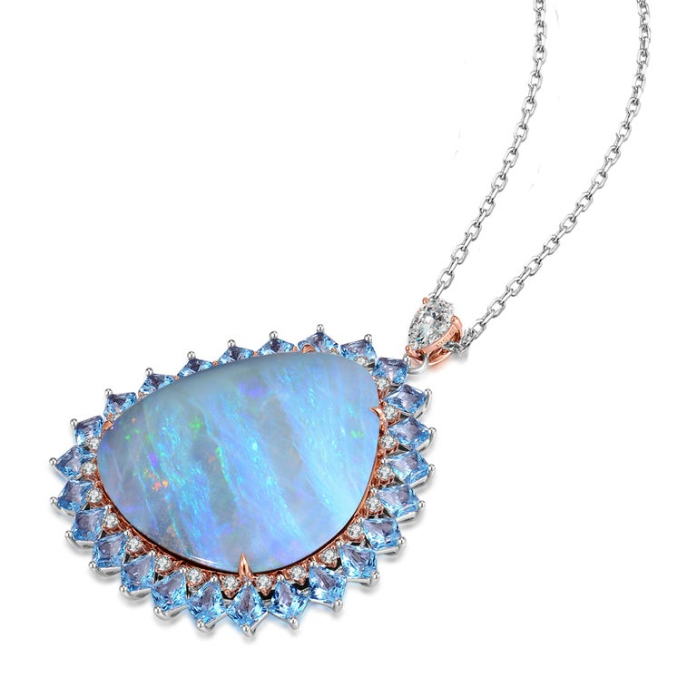 Description: Natural 22.2ct Australian opal with a halo of 0.227ct diamonds and 2.875ct topaz. Set atop is a 0.13ct pear cut diamond set bail. Made in 18ct white gold with accents of 18ct rose gold. Chain length is 16 inches.  Specification: Size