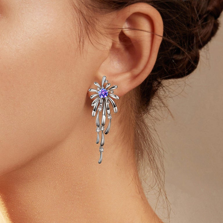 Description: Light up the room with the new Carpe Diem Collection by Fei Liu! Carpe Diem 'Crossette' drop earrings with Swarovski Purple-Aqua Pentagon Star cubic zirconia and 8 hearts and 8 arrows CZ, set in white rhodium plate on sterling