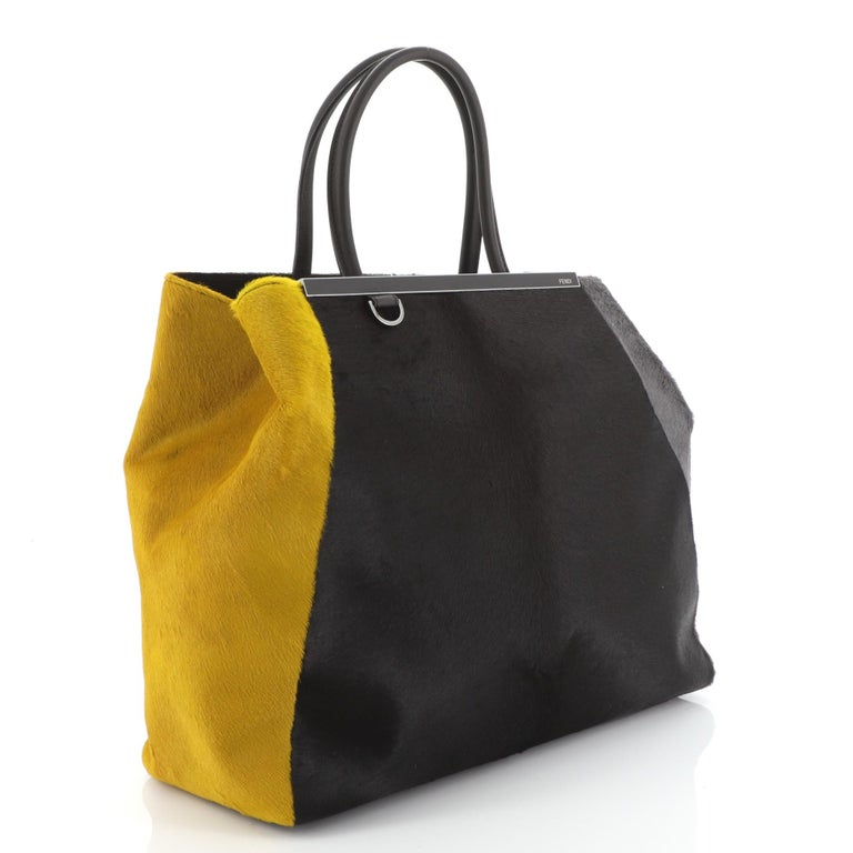 This Fendi 2Jours Bag Calf Hair Large, crafted in multicolor calf hair, features a top bar with the Fendi brand name, dual-rolled leather handles, and gunmetal-tone hardware. Its snap button closure opens to a brown fabric interior with zip pocket.