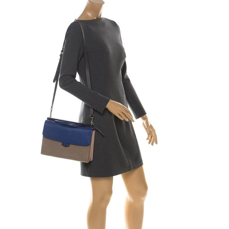 This Demi Jour bag by Fendi is not only lovely to look at, but is also handy and durable. It has been crafted from beige and blue leather and styled very artistically with a flap compartment in the front and a zipper one at the back. The insides are