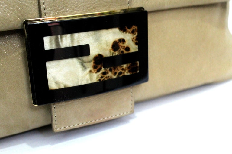 This Fendi shoulder bag has a plastic-covered signature wooden buckle, designer-stamped buckles at front, a magnetic push-stud fastening flap over front, a zip fastening internal pocket!