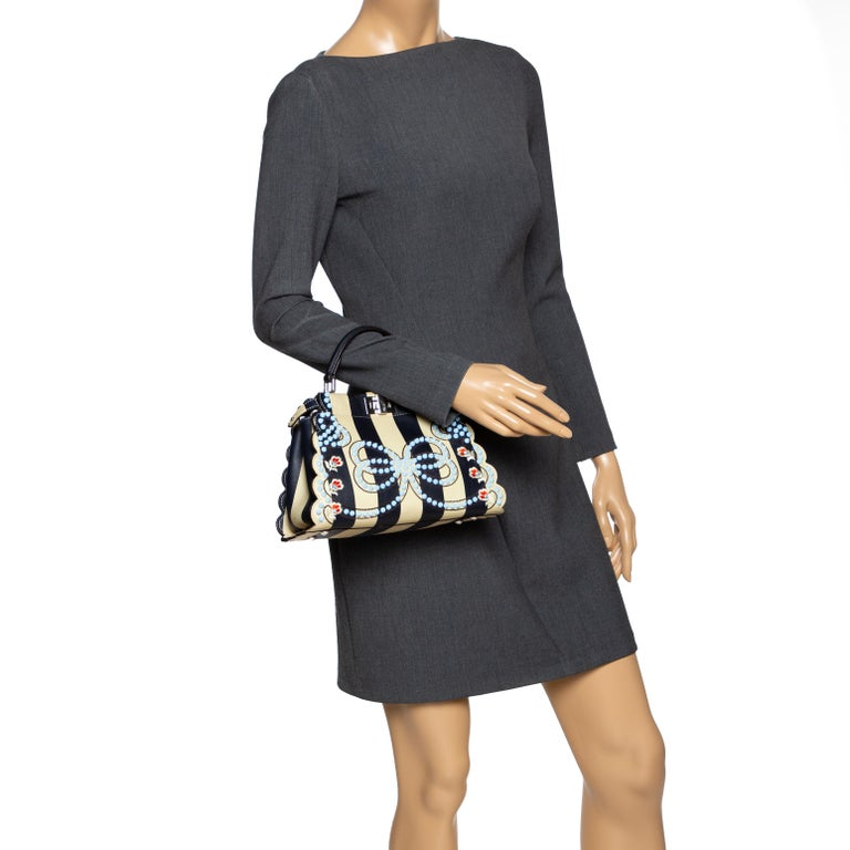 This exquisite Peekaboo from Fendi is highly coveted, and since its birth in 2009, it has swayed us with its shape, design, and beauty. This black & beige version comes meticulously crafted from leather and designed with a top handle for you to