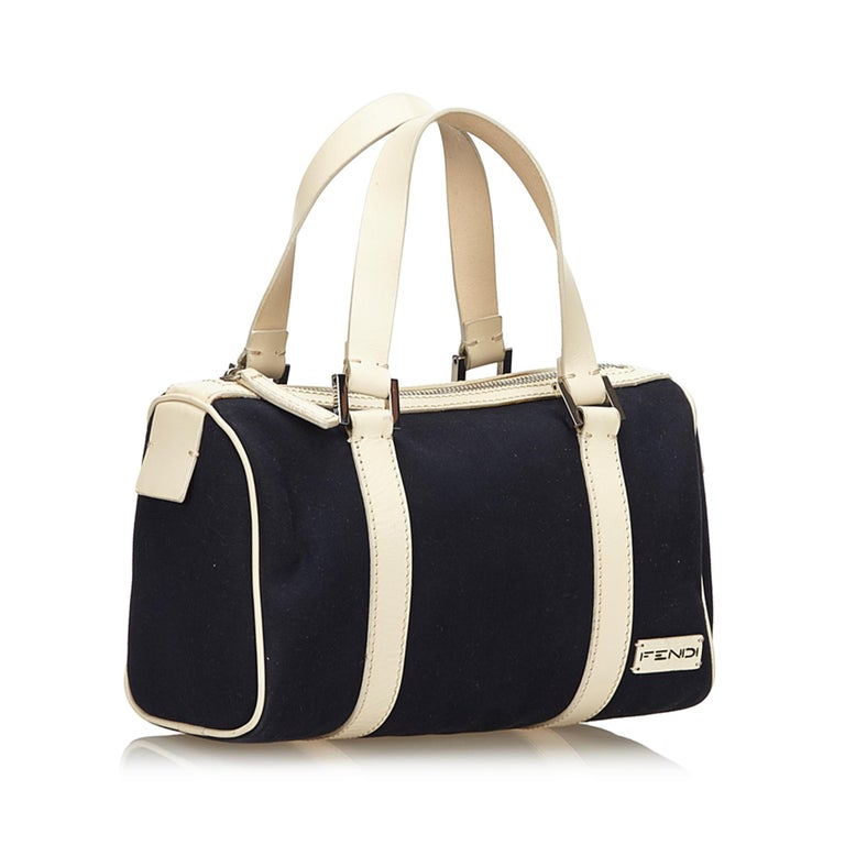 This boston bag features a canvas body with leather trim, flap leather handles, top zip closure, and an interior pocket. It carries as B+ condition rating.  Inclusions:  This item does not come with inclusions.  Dimensions: Length: 17.00 cm Width: