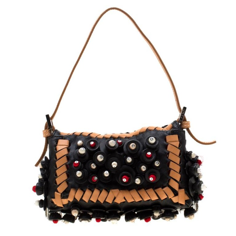 The micro Baguette shoulder bag from Fendi deserves a place in your bag collection. Accented with the striking Forever lock in silver-tone on the front flap, the leather bag has a gathering of embellishments all over the exterior. The interior is