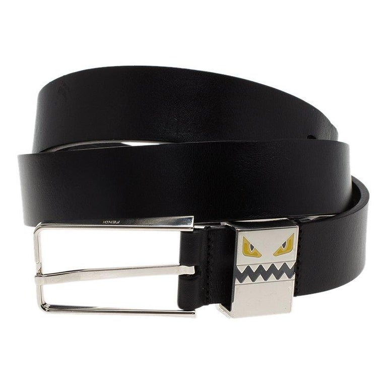 Fendi's signature monster face features on the metal keeper loop of this black leather belt. The slim smooth leather belt has silver toned buckle. Wear the belt to show off the designer brand with its funky trademark face.  Includes: Packaging  The