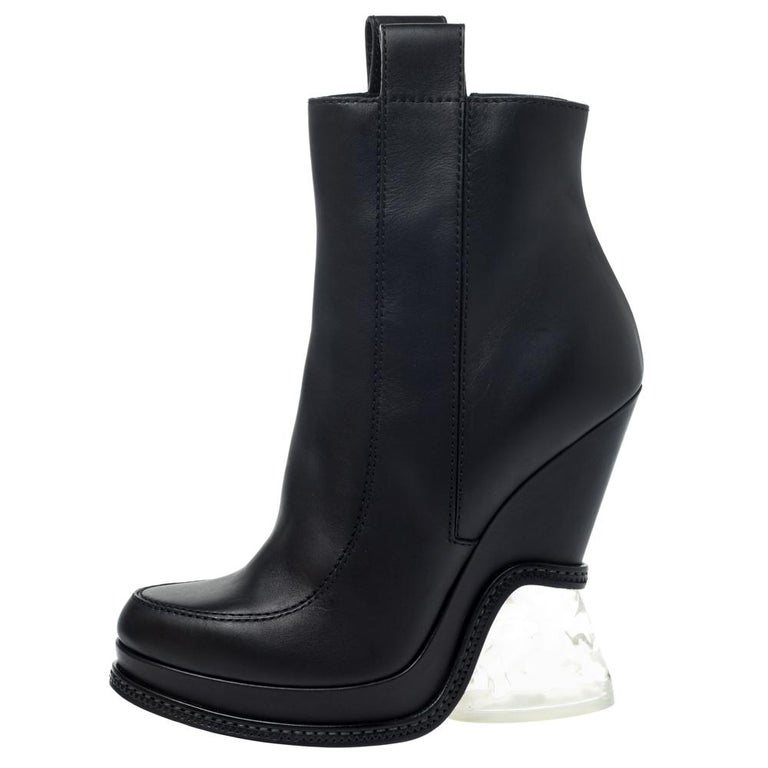 These Fendi boots with round toes and pull tabs are an high-end fashion item that you need to own now. Block transparent lucite heels and neat stitch details on the exterior speak statement. Watch them bring high-octane appeal to all-black evening