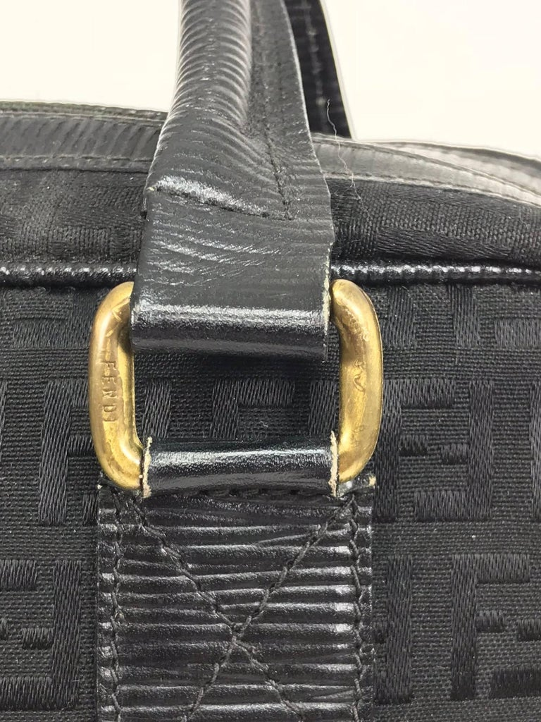 Fendi  black on black logo canvas and leather double handle handbag from the 1970s...Double leather handle bag has a double zipper top closure with a logo pull tabs...Leather trims...Interior in black faux leather with Fendi stamp in gold, a single
