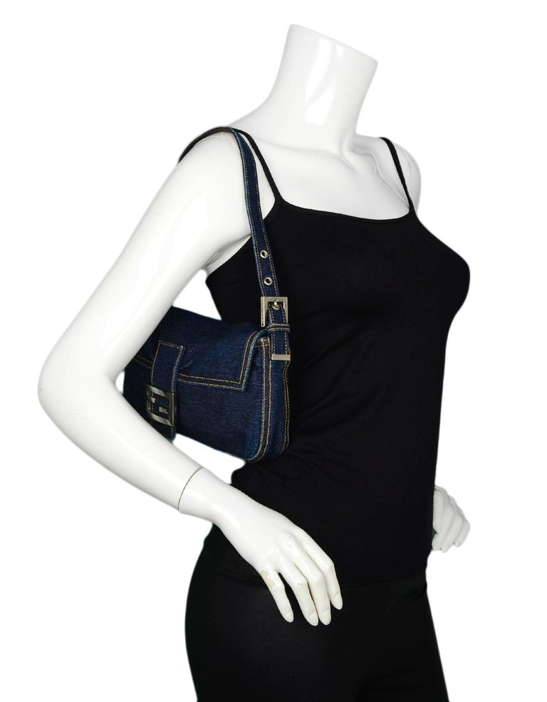 Fendi Blue Denim Baguette Bag W/ Logo Buckle  Made In: Italy Color: Blue, silver Hardware: Silvertone Materials: Denim, metal Lining: Brown logo jacquard textile Closure/Opening: Flap top with magnetic FF logo buckle Exterior Pockets: None Interior