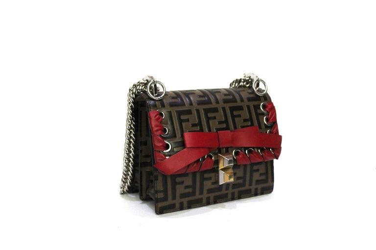 Fendi Kan I line bag made of brown FF leather with red leather details and silver hardware. Closure with hook, internally quite large. The bag is equipped with an adjustable chain shoulder strap, which allows you to wear it as you prefer. The bag is