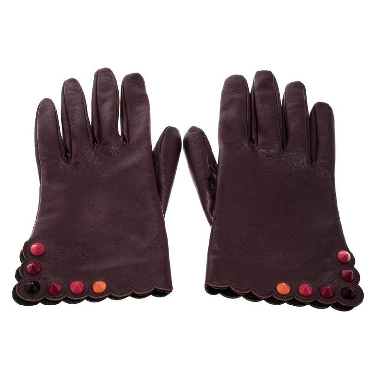 Add a subtle hint of colour to your warm and gloomy winter time wardrobe with this beautiful Fendi pair of gloves. Crafted in burgundy leather, this pair features scalloped edges along with multicoloured studded details along the outer edge of the