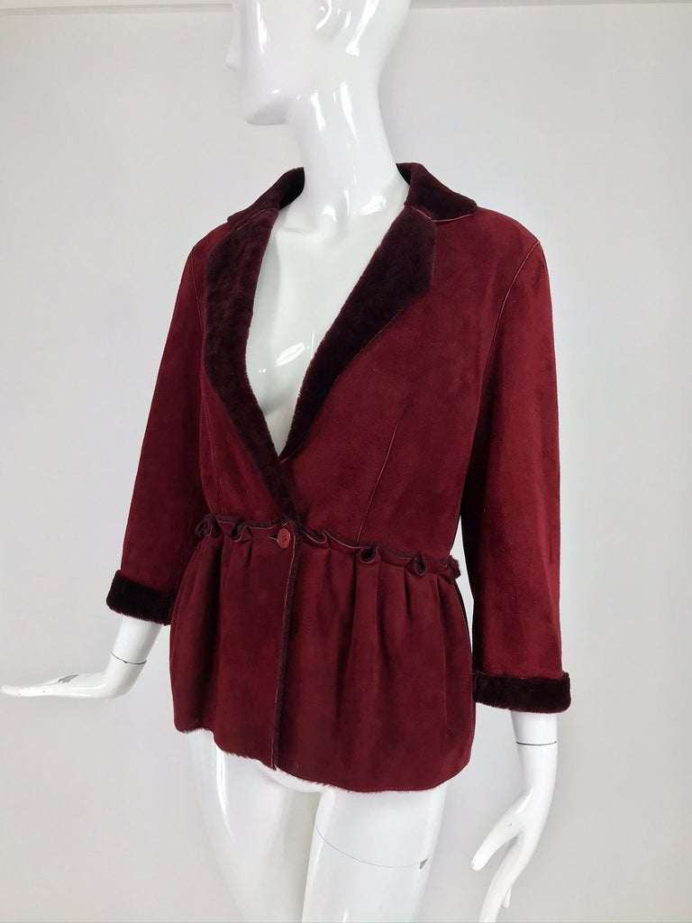 Fendi burgundy shearling button front jacket. Rich burgundy shearling is light and warm, this style could be worn as a layering piece. The jacket closes at the seamed waist front with a single button closure. The jacket  has notched lapels and a