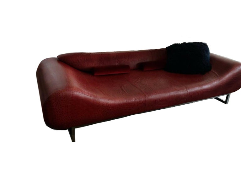 Fendi deep red chestnut leather organic modern 'Eros' Sofa, debuted in 2004.  Fendi casa Eros sofa with steel sleigh legs, adjustable back cushion, embossed pattern at upholstery and brand plaque at lower edge of arm.  MSRP 32,400 USD.