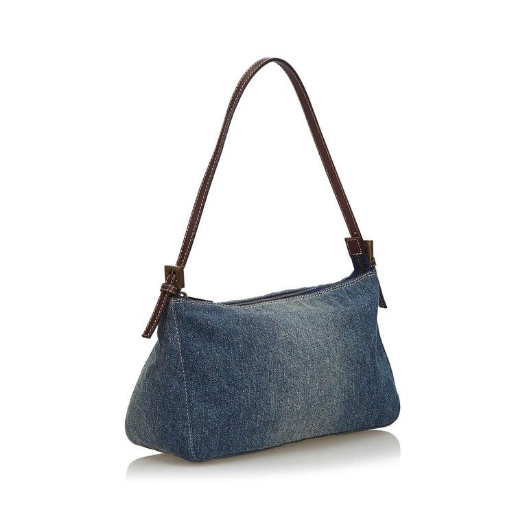 Fendi Denim baguette bag  This baguette features a denim body with leather trim, flat leather strap, and top zip closure.   Approx. 15cm x 25cm x 9cm