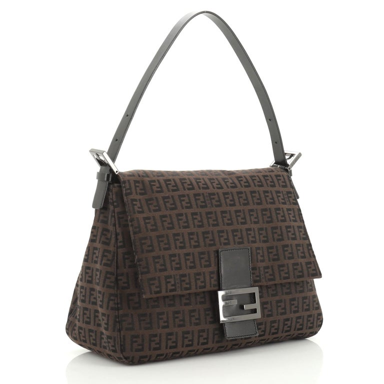 This Fendi Mama Forever Bag Zucca Canvas is a chic piece with FF logo that stands for Fun Fur. Crafted from brown zucca canvas, it features a flat leather strap, Fendi logo detailing, and gunmetal-tone hardware. Its hidden magnetic snap closure