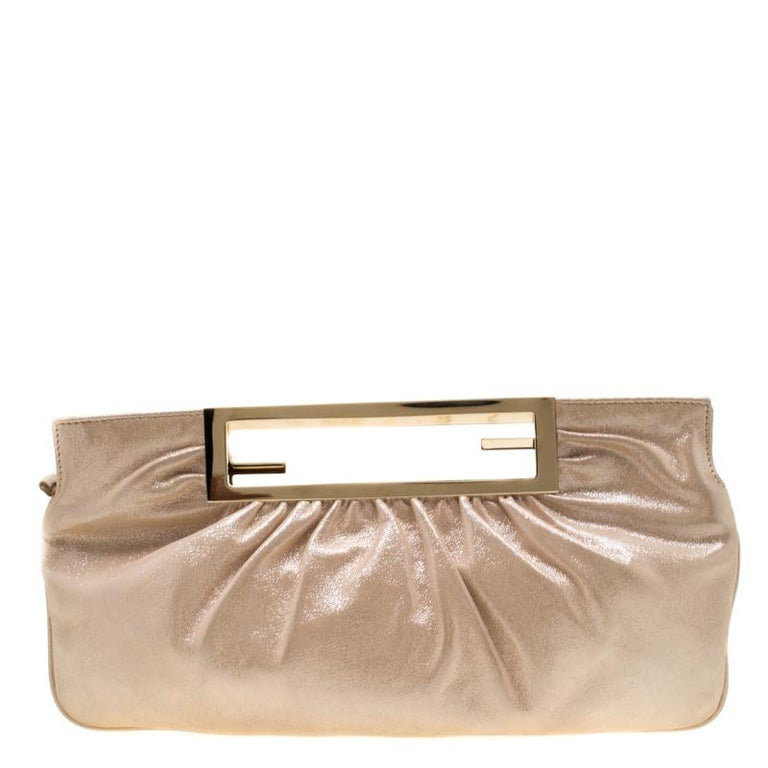 Grab this clutch by Fendi today and make a statement like never before! Crafted from metallic beige leather it features a gold-tone cut-out handle. The satin lined interior is secured by a top zip closure and sized to hold your party essentials.