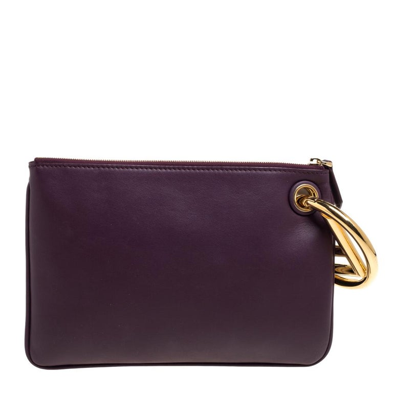 This Fendi Triplette clutch bag is conveniently designed with versatile and functional elements. Edgy and chic, it is crafted from Zucca velvet and leather and assembled with three zipped pouches that are attached to a gold-tone ring, also carrying