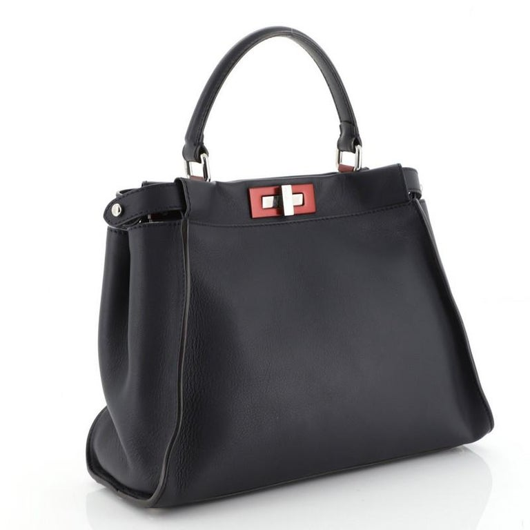 This Fendi Peekaboo Bag Rigid Leather Regular, crafted from blue leather, features a leather top handle, protective base studs, and silver-tone hardware. Its two compartments with turn-lock and zip closures open to a blue leather and suede interior