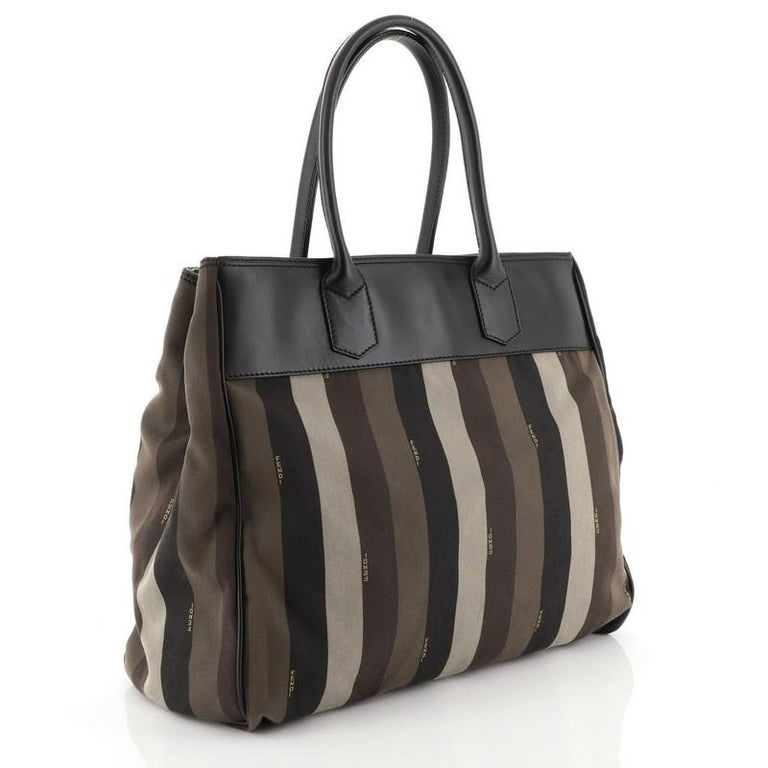 This Fendi Pequin Tote Canvas with Leather Large, crafted in brown canvas and black leather, features dual rolled leather handles, leather trim, and gunmetal-tone hardware. It opens to a brown fabric interior with middle zip compartment and side