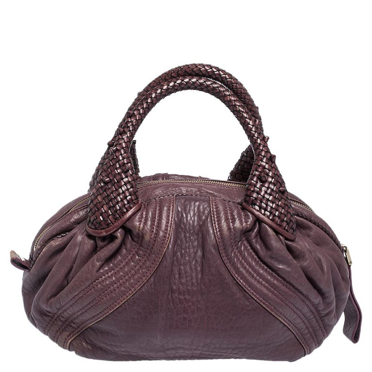 This chic Spy bag is from Fendi. The bag is crafted from leather and features two woven handles on top. The bag also comes with a fabric interior that can fit all your daily essentials. Flaunt this beauty wherever you go and you will surely receive