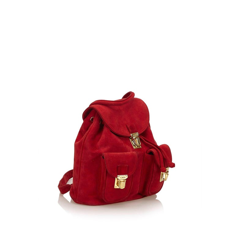 This backpack features a suede leather body, exterior front flap pockets, flat back straps, top flap with push lock closure, drawstring closure, and interior slip pocket.   It carries a B+ condition rating.  Dimensions:  Length 27 cm Width 25