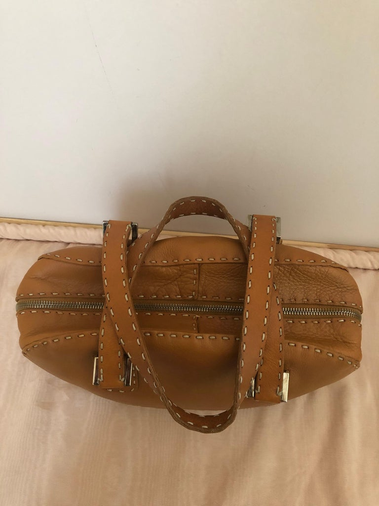 Very elegant and wearable  Fendi tan/cognac grain leather, with wide top stitch, and a sterling silver oval tag on the outside of the inside zipped pocket. The dual handles are flat and wide stitched, and the silver handle hardware incised with