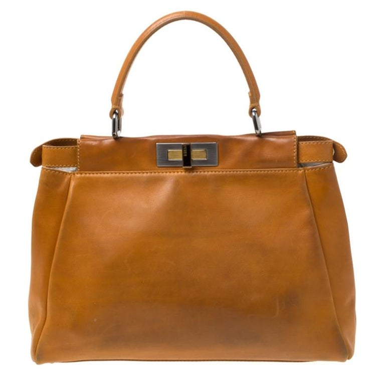 This exquisite Peekaboo from Fendi is highly coveted, and since its birth in 2009, it has swayed us with its shape, design, and beauty. This version comes meticulously crafted from leather and designed with a top handle for you to swing it. A