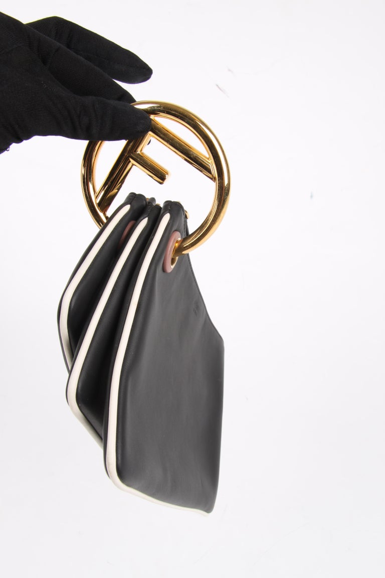 Fendi designed this sturdy combination of three clutches in small, medium and large.  They are dangling together on a large gold-tone ring with a Fendi F. All bags have a white trim, top zip closure and black softly shiny lining.  The bags can be