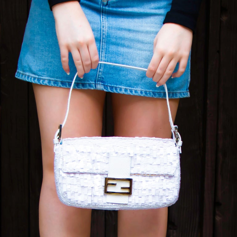 Beautiful White Python Baguette Handbag. This bag has one main pocket and a small zippered section. The outside is white sequence and the leather aspects of the bag are python. Made in Italy.  Height = 6 inches Width = 10 inches Depth = 2.5 inches